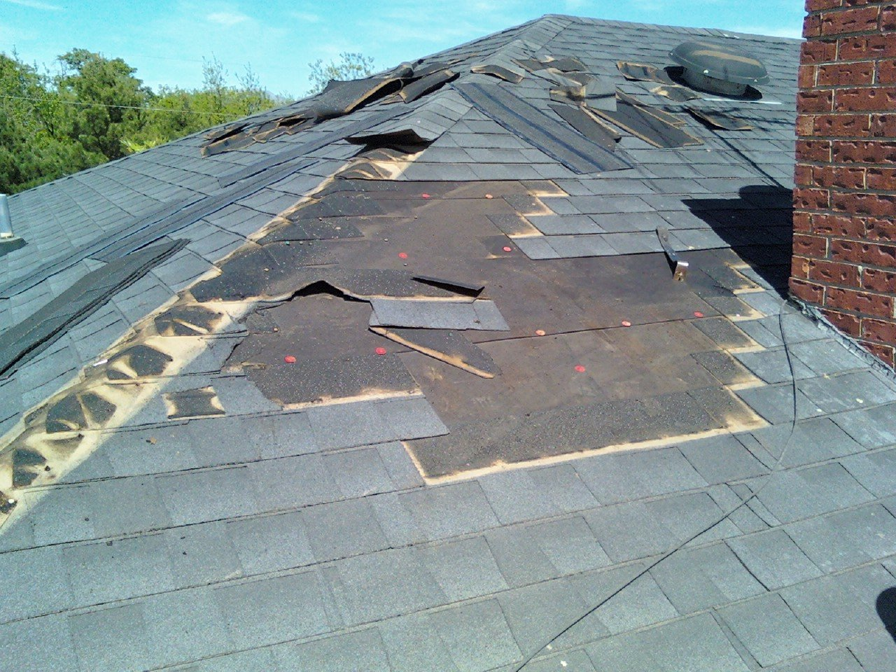 Roof repair. A damaged roof with missing shingles.